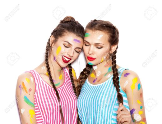 Smeared in paint girl friends posing with closed eyes. White background not isolated